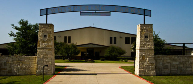 Front enterance of Whispering Farms Equestrian Center. Sign above drive way and beige building in back.