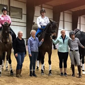 Three horses two with riders and four other ladies stand beside in the indoor arena after great lessons for Whispering Farms