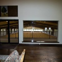 View from upstairs area with brown floor and tan walls overlooking the indoor arena below for Rider Amenities