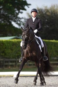 Black horse in outdoor show arena with rider in black coat and white breeches with white rail behind and green hedge in the background for Claudio Olivera Dressage Clinic