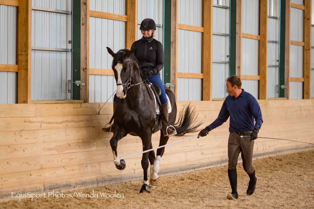 Rider with black top and blue breeches on bay horse with big blaze on face work along a wooden wall with trainer beside on the ground assisting with small bamboo rod for Claudio Olivera Dressage Clinic