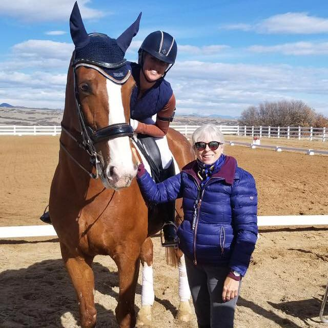 Big chestnut horse in a double bridle and a blue fly bonnet with rider atop stand next to trainer in a blue parka in an outdoor arena with blue sky and hills in the background for Dolly Hannon Dressage Clinic