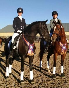 Two horses with champion sashed around their neck with riders atop standing in an outdoor arena with a beige barn in the background on a sunny day for Dolly Hannon Dressage Clinic