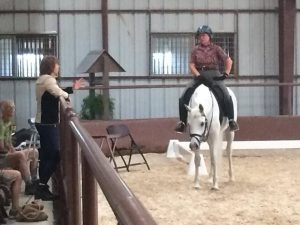 White horse stands in indoor arena on sandy footing with rider atop next to rust colored pipe railing with trainer standing and instructing for Clinics