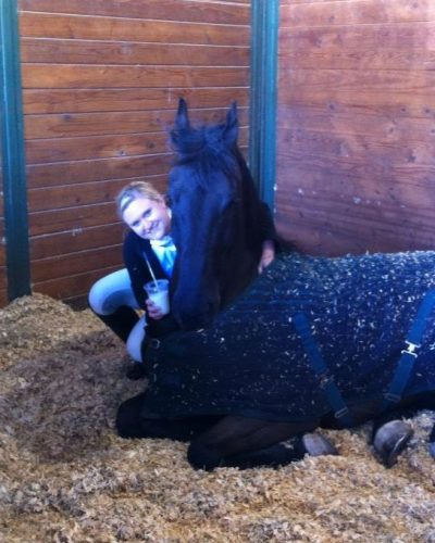 Black horse curled up and laying down in a stall with shavings wearing a blanket and with a lady kneeling next and giving a hug for Katie McCullough